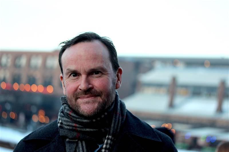 Bildet er av Per Fikse. Han har på mørk jakke og skjerf. I bakgrunnen er det bygninger som er ute av fokus. Han har mørkt hår og kort skjegg.