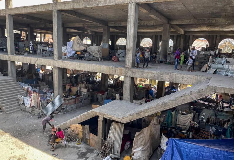 Bildet er av flyktninger som bor midlertidig i restene av en skolebygning. Det er bar betong og ingen vegger.
