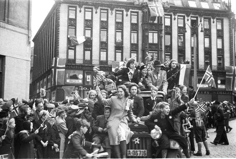 Bildet viser en gruppe mennesker som jubler i Oslo sentrum. Krigen er over. Bildet er i svart og hvitt.