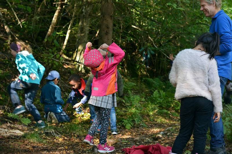 Bildet viser en jente som jubler over å ha kommet i mål. Barna lærer gjennom lek og oppgaver.