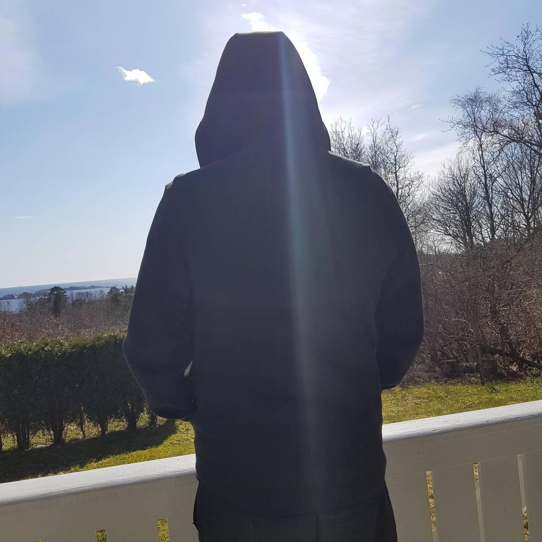 Bildet viser en person som står med ryggen til.
