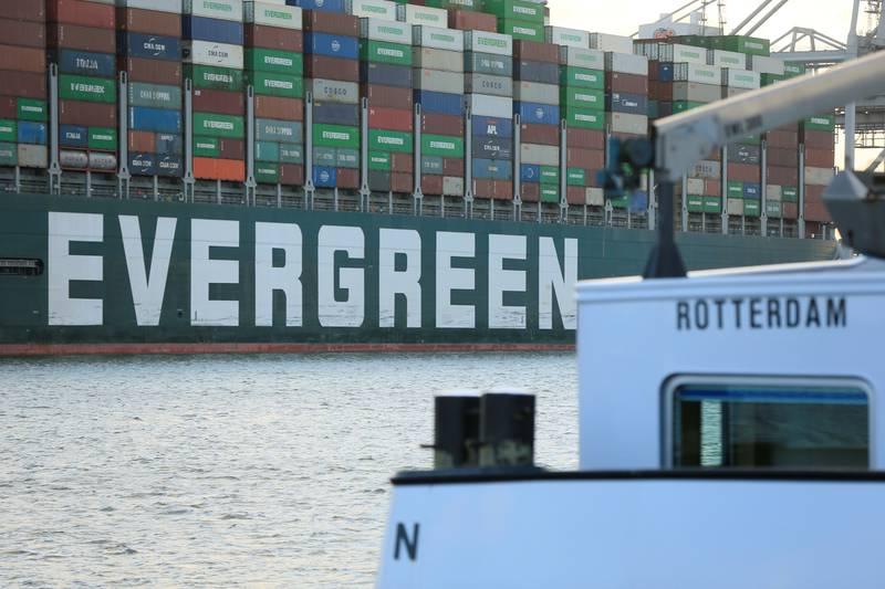 Bildet er av den ene siden av skipet Ever Given. Det står Evergreen i hvitt på siden av det mørkegrønne skipet som er lastet med store mengder konteinere i ulike farger. I forgrunnen av bildet er også en liten hvit båt der det står Rotterdam. Foto: Eva Plevier / Reuters / NTB