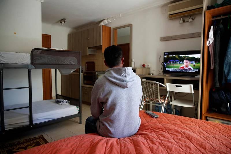 Bildet viser ryggen til en mann som sitter i et rom og ser på TV.